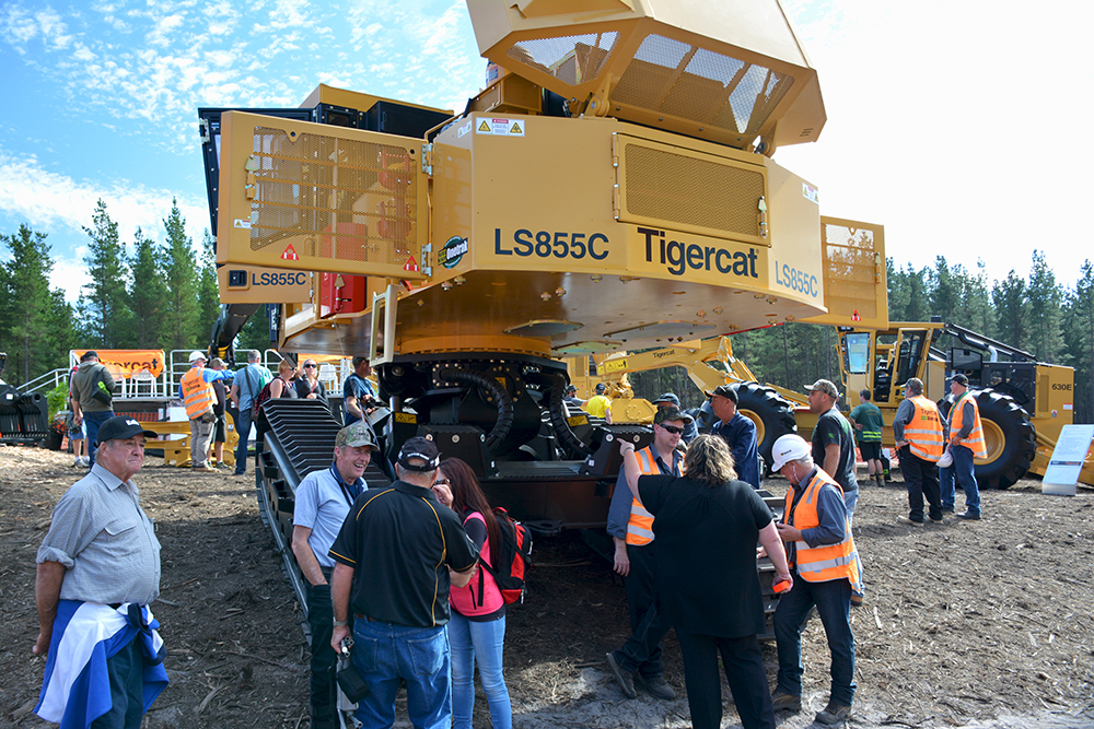 Customers check out the massive pins and thick steel plate on Tigercat's patented leveling system of the LS855C shovel logger.