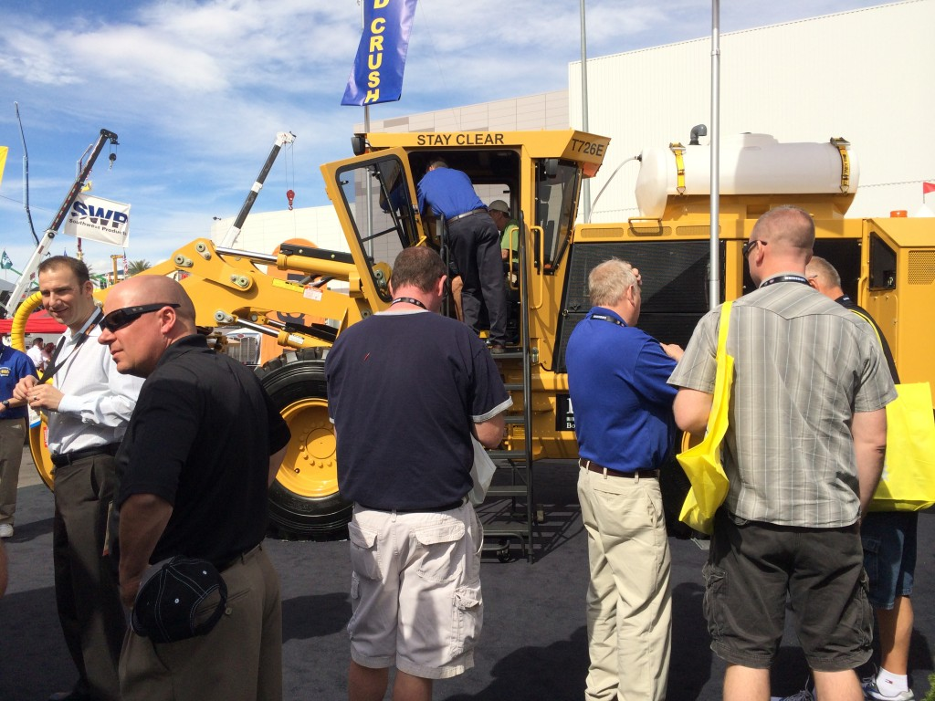 A group of people stand intrigued around the Tigercat T726E trencher