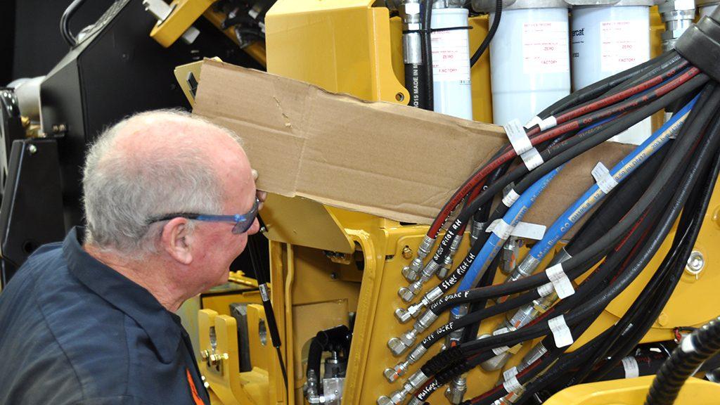 Un technicien vérifiant la présence de fuites hydrauliques à l'aide d'une feuille de carton.