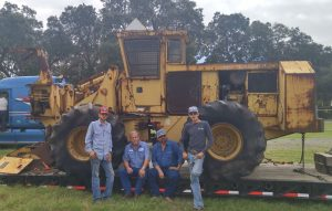 4 men stand in front of a old worn down machine; the first ever Tigercat built. The machine is on a truck trailer, ready to be taken back to Canada.