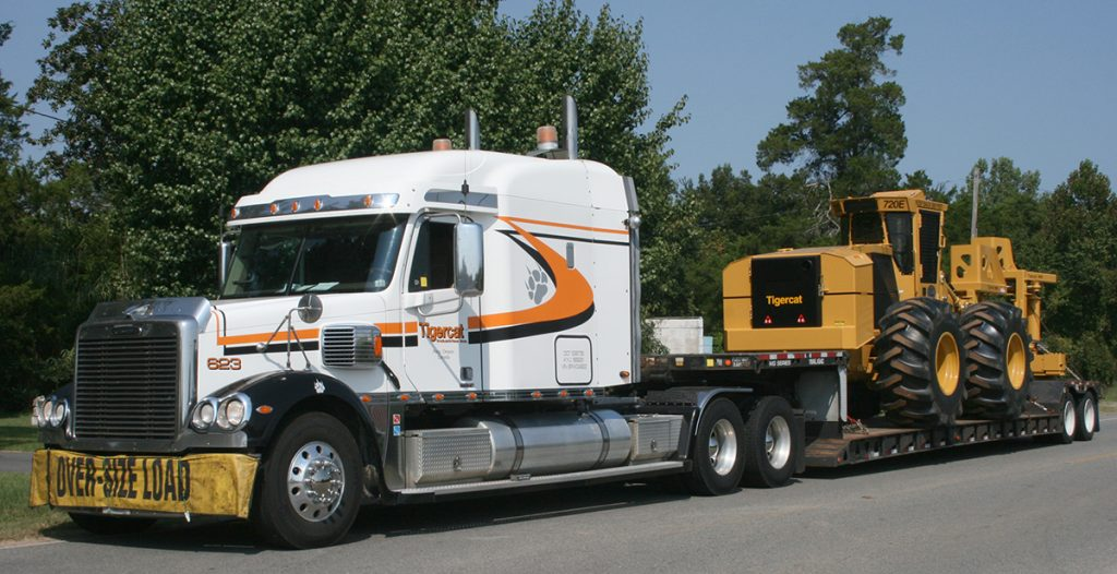 The 10,000th machine being delivered by a Tigercat transport truck.