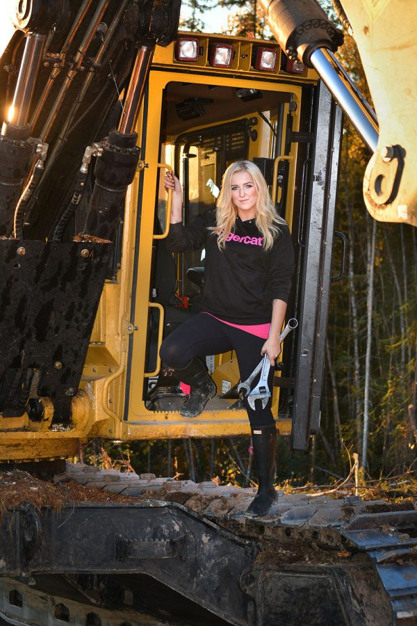 Passionate forestry equipment female operator, Hannah Dehoog of Smithers, British Columbia standing in the front door of her cab with wrenches in her hand wearing a Tigercat sweater.