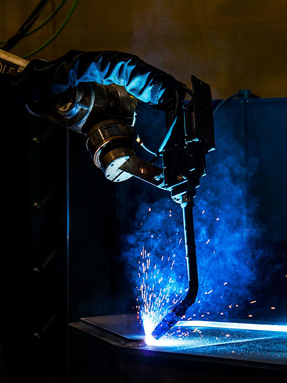 Des étincelles bleues produites par le nouveau bras de soudage robotisé de Tigercat, fabriqué par Wolf Robotics, soudant des pièces.